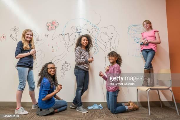 Girls drawing on whiteboard