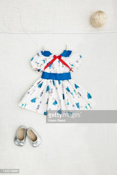 Girl's dress and shoes hanging on wall