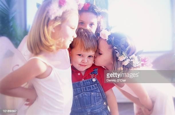 Girls (4-6) dressed as fairies kissing boy