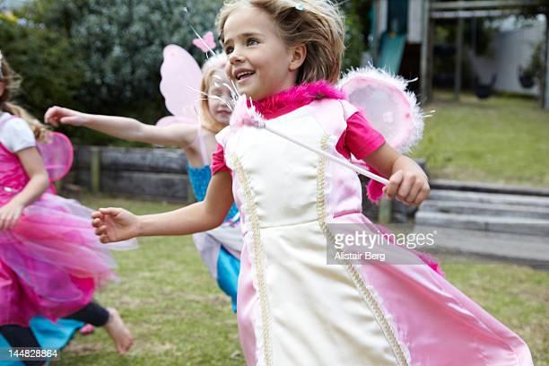 Girls dressed as fairies running in garden