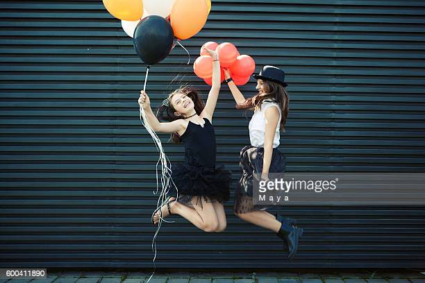 Girls dressed for Halloween jumping with balloon