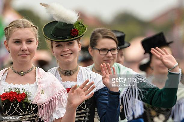 Girls dressed in Bavarian folk outfits wave in the Parade of Costumes and Riflemen on the second day of the 2015 Oktoberfest on September 20 2015 in...