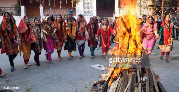 Girls dressed in their traditional attire dance around a bonfire as they celebrate Lohri festival on January 13 2018 in Jammu India Lohri is a great...