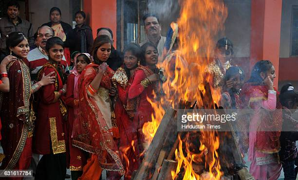 Girls dressed in traditional attire dance around a bonfire as they celebrate Lohri festival on January 13, 2017 in Jammu, India. Lohri is a harvest...