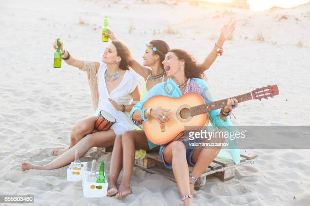 Girls drinking beer and playing guitar on beach