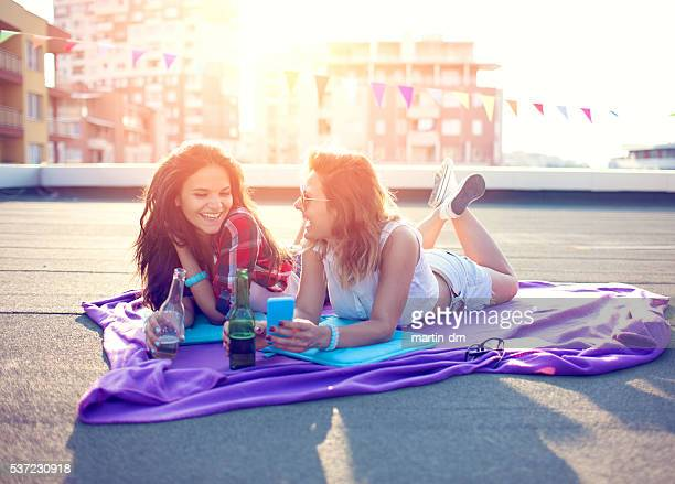girls drinking beer on the rooftop - girls sunbathing stock pictures, royalty-free photos & images