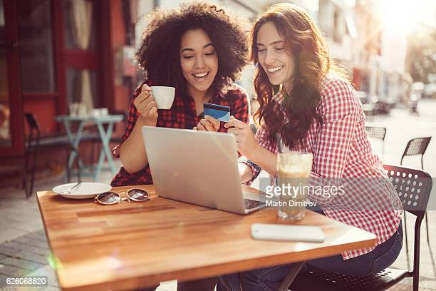 girls drinking coffee and shopping online - saturday stock photos and pictures