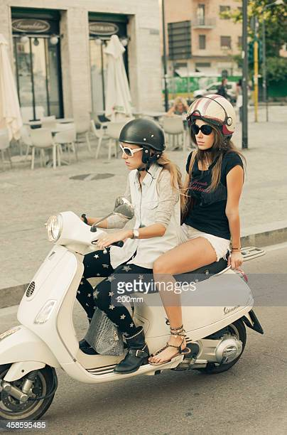 girls driving vespa scooter - vespa brand name stock pictures, royalty-free photos & images