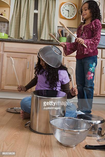 Girls drumming on pots and pans in kitchen
