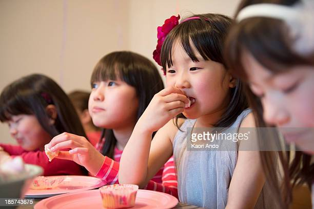 girl's eating fairy cakes at party - cobham surrey stock pictures, royalty-free photos & images