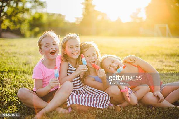 girls eating flavored ice in sunny field - popsicle stock pictures, royalty-free photos & images