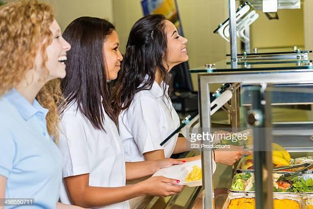 Mädchen isst Mittagessen im privaten high school-cafeteria