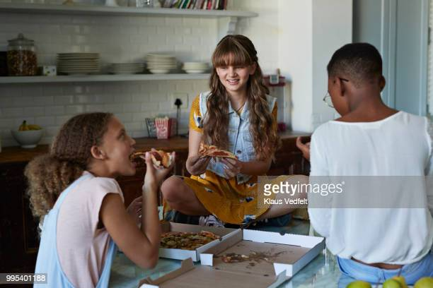 3 girls eating pizza at home