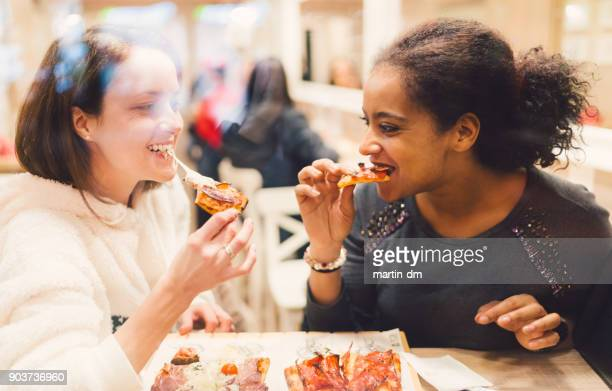 girls eating pizza - pizzeria stock photos and pictures