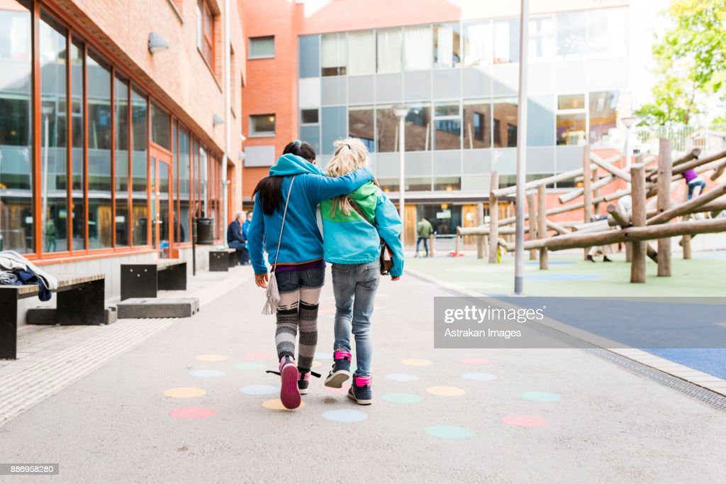 Girls (8-9) embracing and walking together : Foto de stock