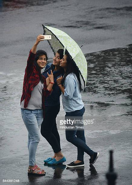 Girls enjoy and take selfie in the pleasant weather during rain at Ridge on July 2 2016 in Shimla India The minimum temperature of Shimla was 156...