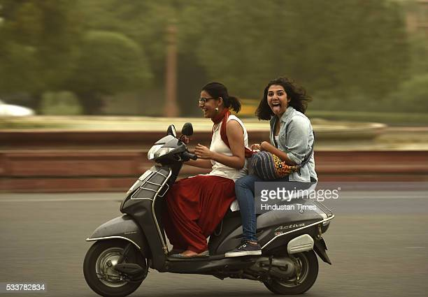 Girls enjoy bike ride in pleasant weather after the dust storm and rain on May 23 2016 in New Delhi India Sudden rains brought respite for people in...