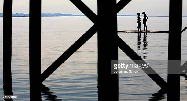 Girls enjoy the warm weather at the beach of Lake Constance on April 17 2007 near Lindau Germany The unseasonably warm weather has heralded the start...