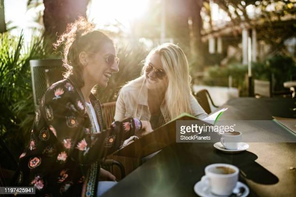 filles appréciant à l'extérieur - terrasse de café photos et images de collection