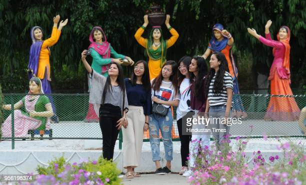 Girls enjoying the weather at Verka Park on May 8 2018 in Mohali India Dust storms rain and thunder lashed out in parts of northern India uprooting...