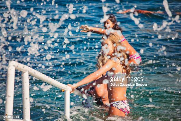 Girls entering the sea while the waves crash and splash