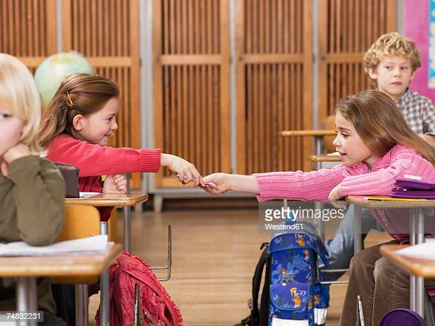 Girls (4-7) exchanging notes in classroom