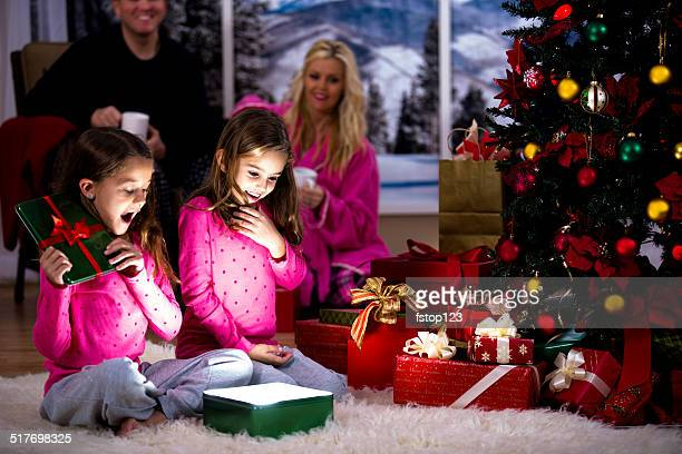 Girls excitedly open Christmas presents. Parents, tree, gifts background.