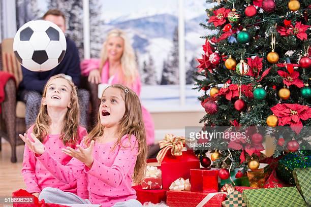 Mädchen excitedly öffnen Weihnachten präsentiert.  Fußball ball.  Eltern, Baum und Geschenke.