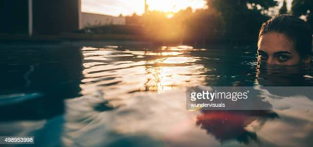 Girl's face half submerged in a late evening swimming pool