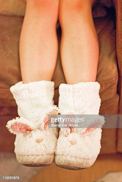 Girl's feet in bunny slippers, dangling off floor