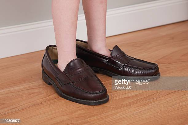 Girls (6-7) feet in father's shoes