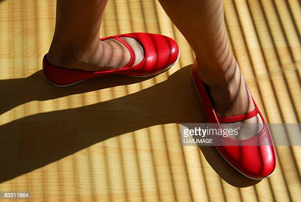 girl's feet in red shoes - 赤の靴 ストックフォトと画像