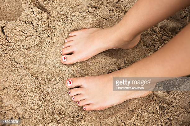 Girls feet in the sand with hearts on the nails