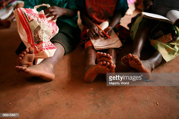 Girls' feet stretch out on the floor of a classroom at Namaripe Primary School in Zambezia province March 10 2010