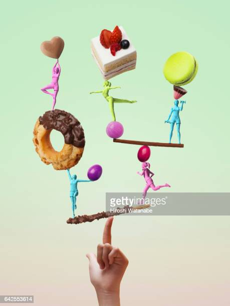 girls figures taking a balance while exercising with sweets - digital desire fotos stock-fotos und bilder