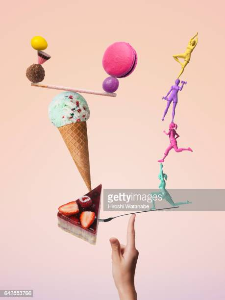 Girls figures taking a balance while exercising with sweets