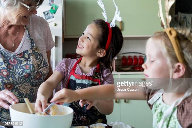 Girls filling cupcakes for Christmas whilst looking at grandmother