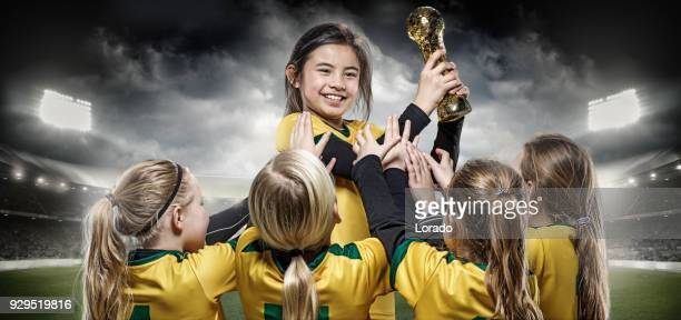 girls football team celebrating with soccer trophy - sports team event stock photos and pictures