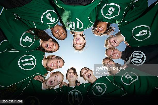 girls (12-15) football team forming huddle, view from below - 足球 團體運動 個照片及圖片檔