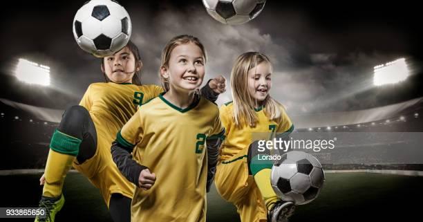 équipe de football de filles posant pour des photos de l'équipe de football action dans un stade éclairé - par équipe photos et images de collection