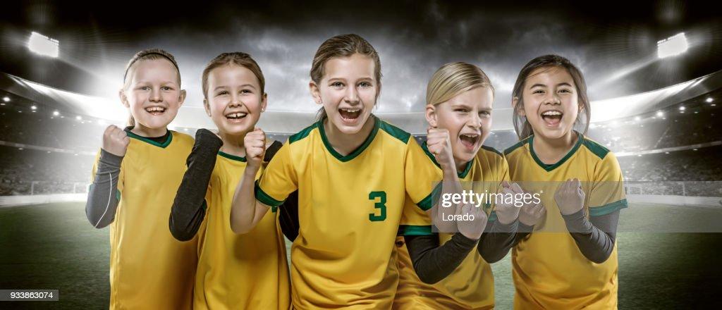 Girls football team posing for soccer team photo in a floodlit stadium : Stock Photo