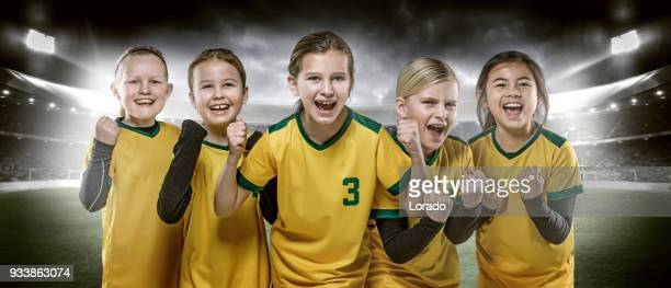 girls football team posing for soccer team photo in a floodlit stadium - sports team event stock photos and pictures