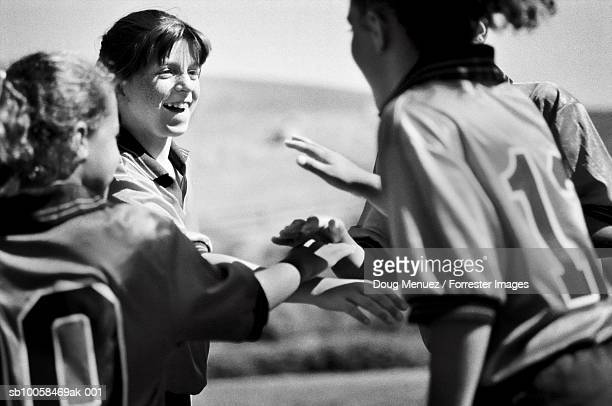 Girls football team with hands together, outdoors (B&W)