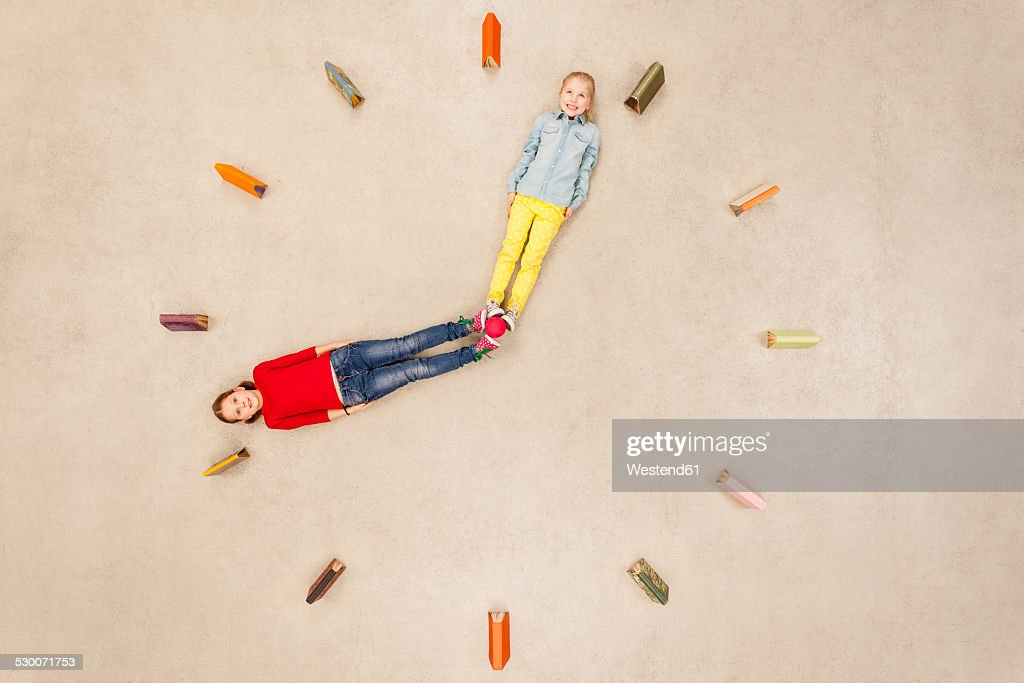 Girls forming clock needles : Photo