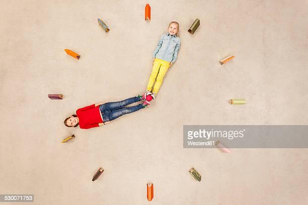 Girls forming clock needles