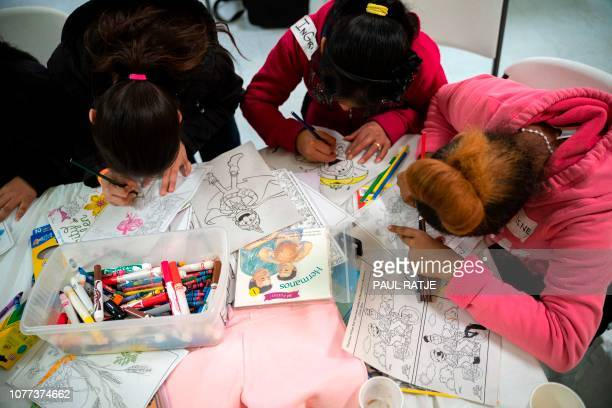 Girls from Central America spend time coloring the night of their release from immigration detention at the Basilica of San Albino in Mesilla New...