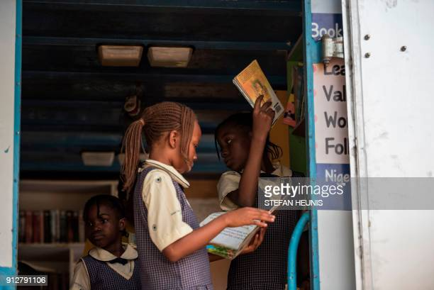 Girls from the Bethel Nursery and Primary school browse through the books in the IRead mobile library on January 30 2018 The IRead initiative is the...