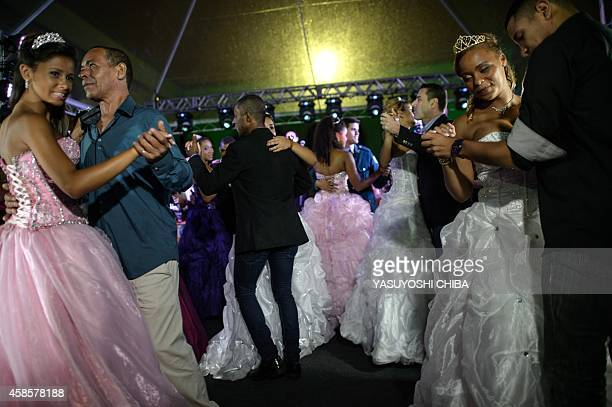 Girls from the CerroCora favela who turn 15 this year dance a waltz with family members during their group debutante ball organized by the Pacifying...