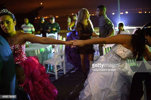 Girls from the CerroCora favela who turn 15 this year dance during their group debutante ball organized by the Pacifying Police Unit from their...