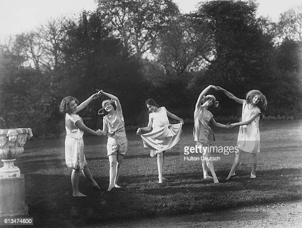 Girls from the Italia Conti Stage School practice ballet steps on the lawn